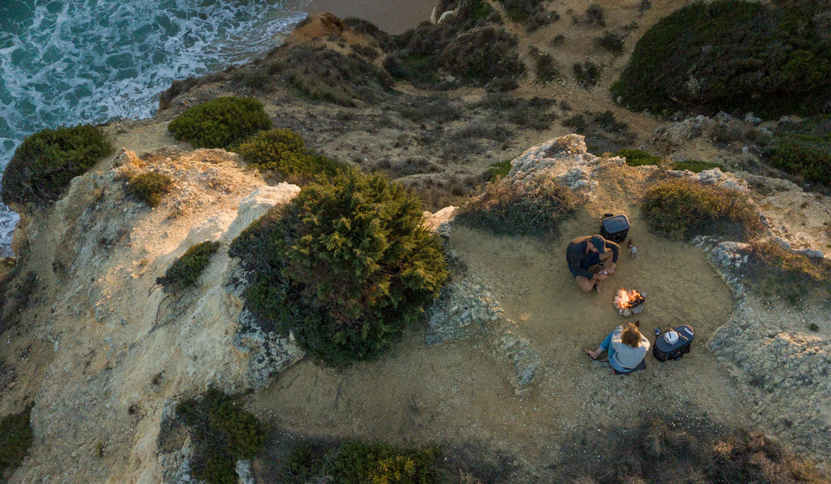 couple having a BBQ on top of a cliff with a Red Original waterproof cooler bag