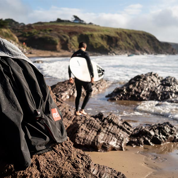Man in a wetsuit carrying his surfboard to the beach with his changing robe left on a rock