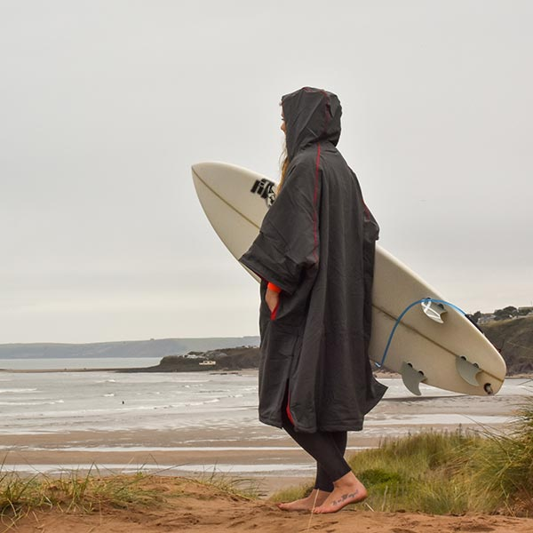 Woman in changing robe carrying her surfboard to the beach