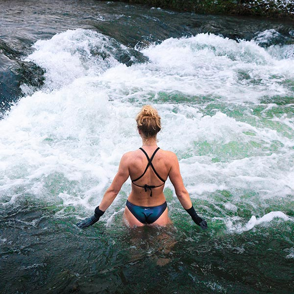 Woman walking into cold running river