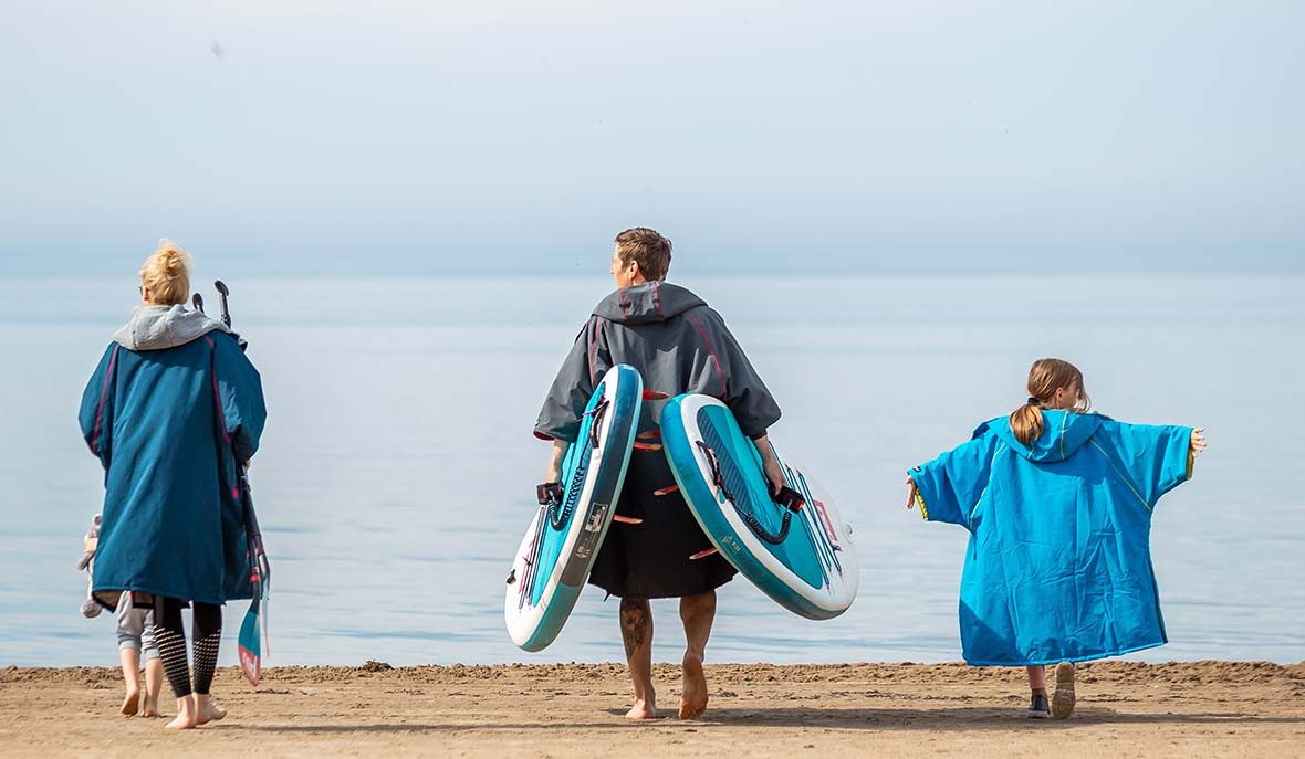 Family of 3 walking toward the sea carrying paddle boards