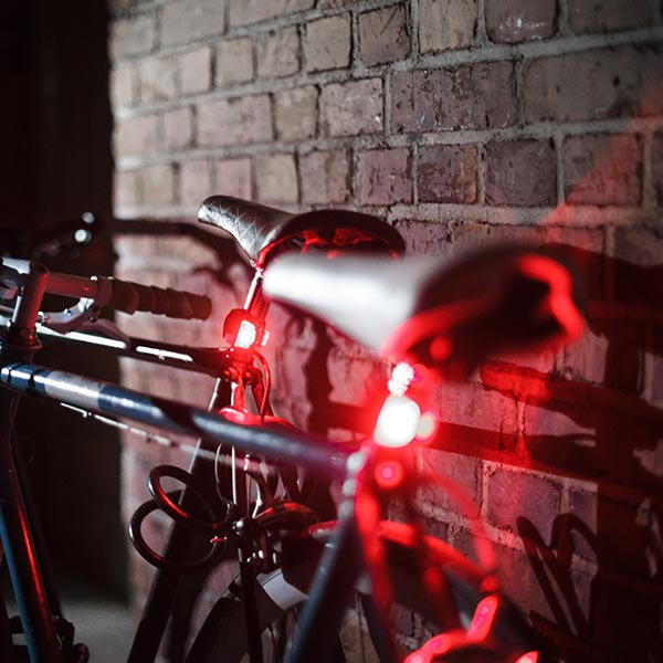 A bike up against a wall with its lights on