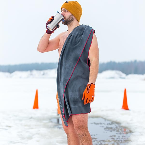 Man on Snowy Beach with a swimming cap and microfibre towel