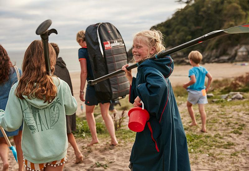 Girl wearing  kids changing robe carrying a paddle and a plastic bucket