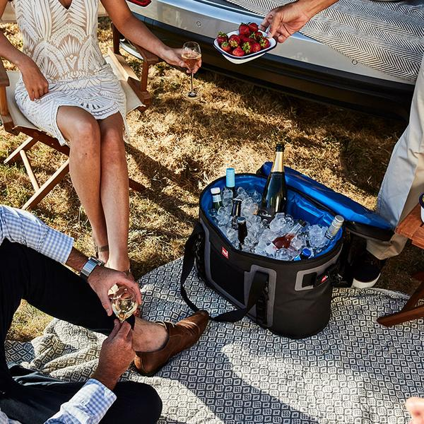 People sat around a waterproof cooler bag filled with drinks and ice