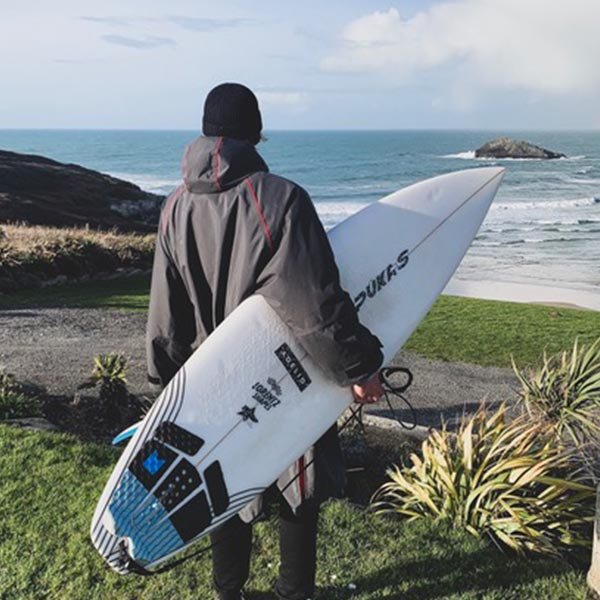Man carrying a surfboard to the beach