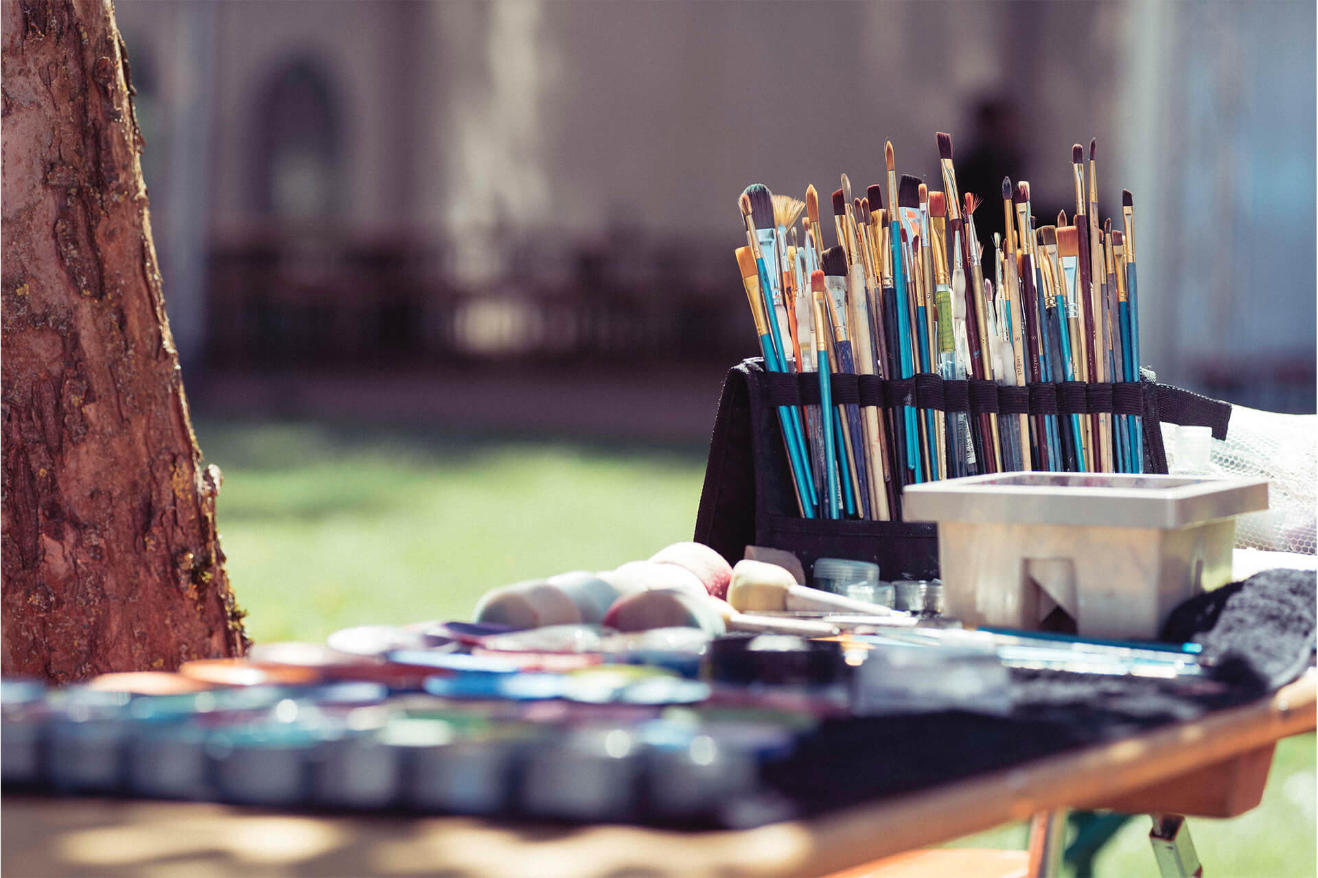 Outdoor painting set up with a number of brushes and paints on a table next to a tree