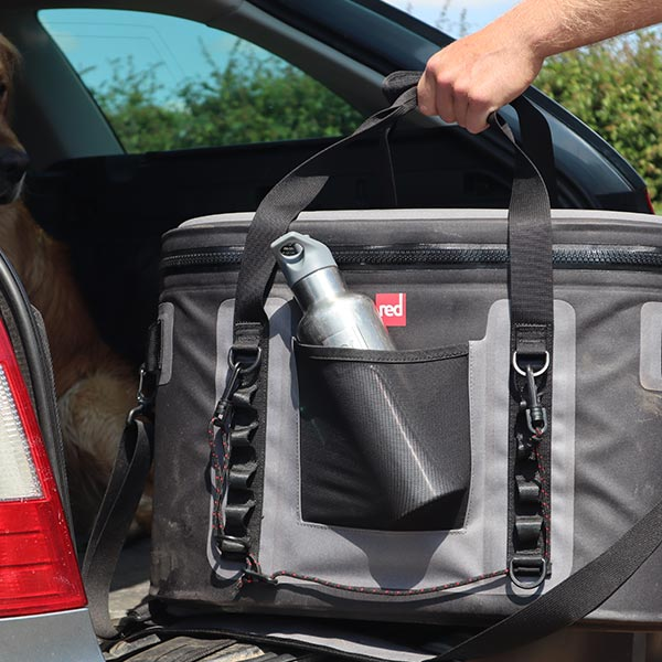 Red Original Cooler Bag With A Water Bottle in the front pocket being loaded into a car