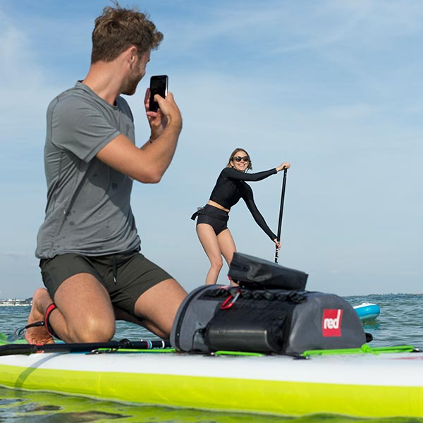 Man kneeling on his paddle board while taking a photo of a woman paddling