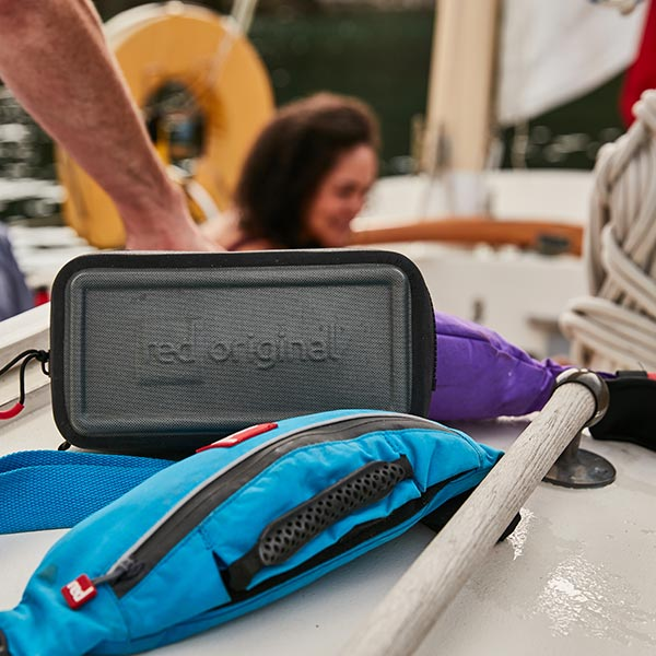 A Red Original Waterproof Pouch and PFD on a sailing boat