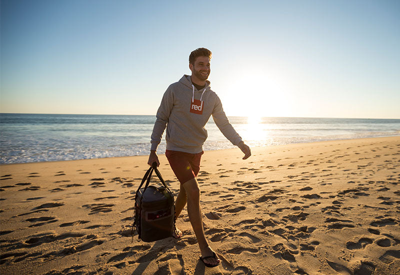 man on beach at sunset wearing red original grey hoody