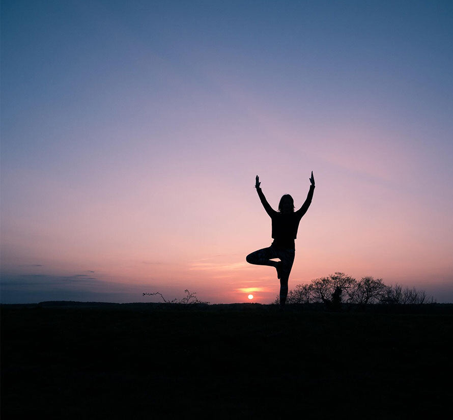 Woman practicing outdoor Yoga at dusk