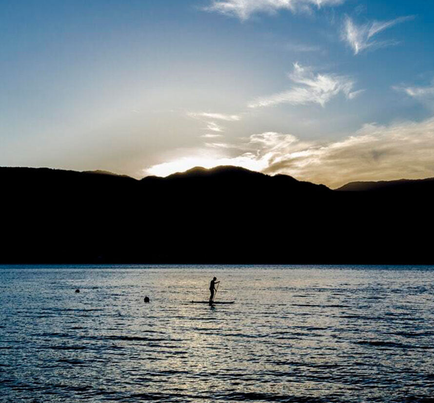 Person paddleboarding in the sea at dusk