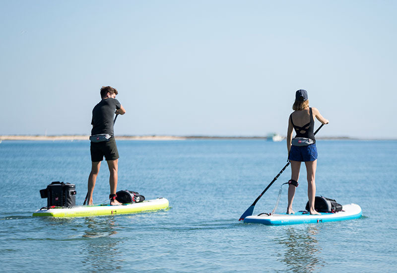 Couple paddle boarding wearing Red Original Airbelt PFDs