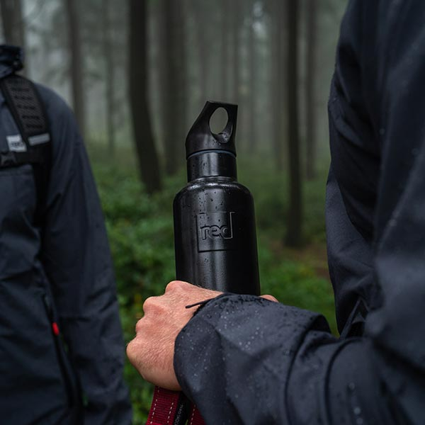 Man in a forest holding a black reusable water bottle from Red Original