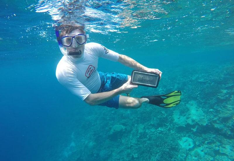 Man swimming underwater with a waterproof pouch