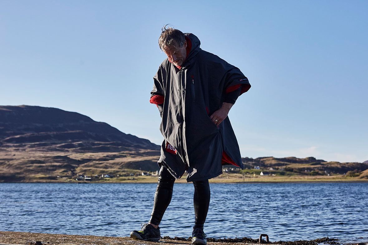 Man standing on the beach wearing a Red Original Pro Change Robe