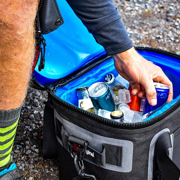 Man pulling a can out of a cooler bag filled with ice