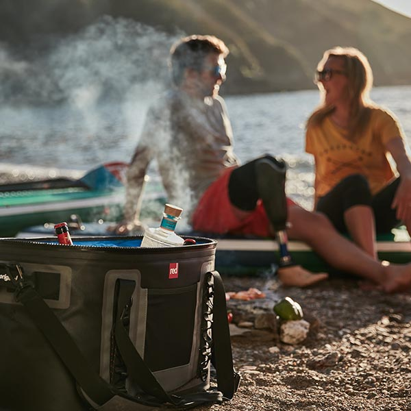2 people sat on decking with a cooler bag in the foreground