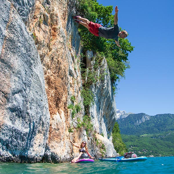 Paddle Boarding by a cliff as someone dives into the water