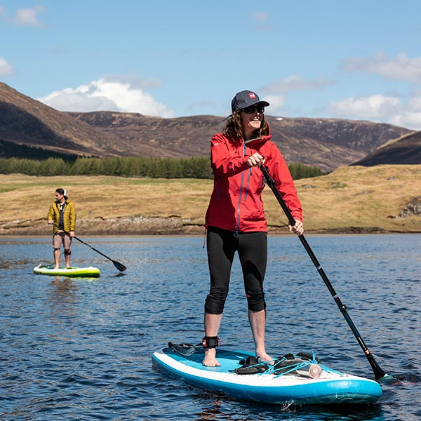A Man And A Woman Paddle Boarding on a Lake
