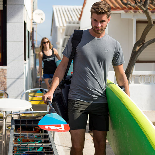 Man walks carrying paddle board wearing Performanc T shirt.