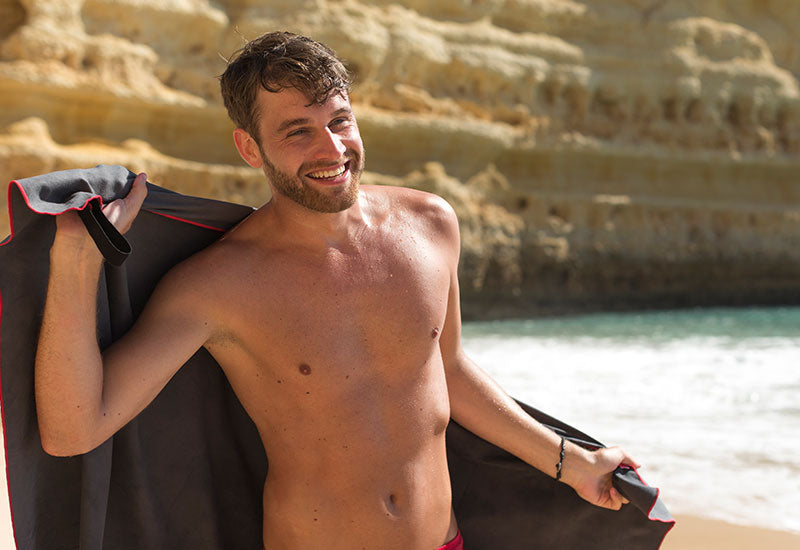 man drying himself on the beach with Red Original Microfibre Towel