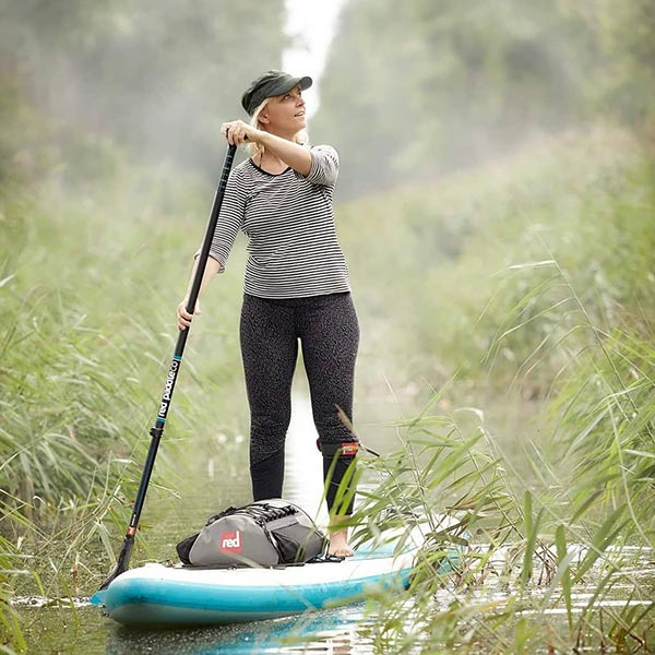 Woman Paddle Boarding Through Some Reeds