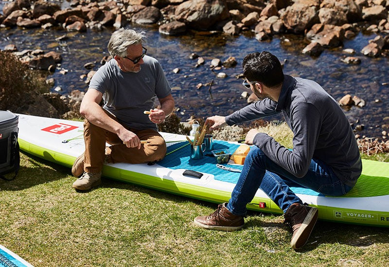 2 Men Enjoying A Snack On A Paddle Board