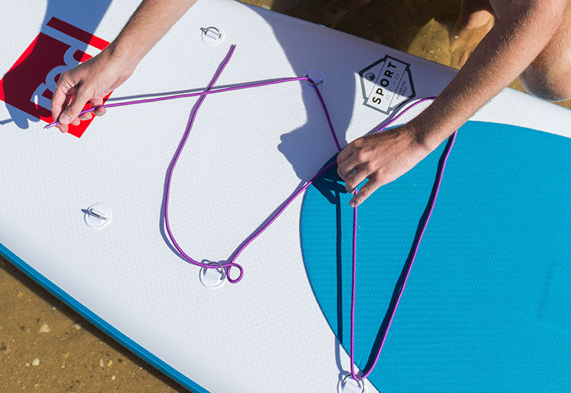 threading the Red Original Purple Cargo Bungee through the cargo points on a SUP
