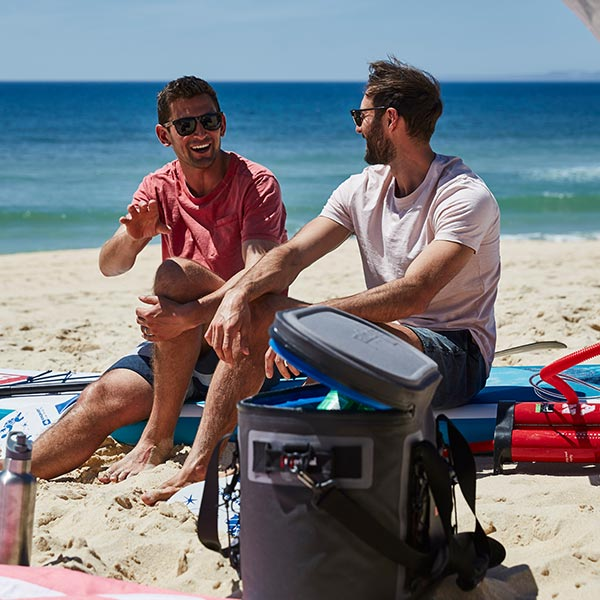 2 Men Sitting On The Beach Enjoying A Drink From A Cooler Bag