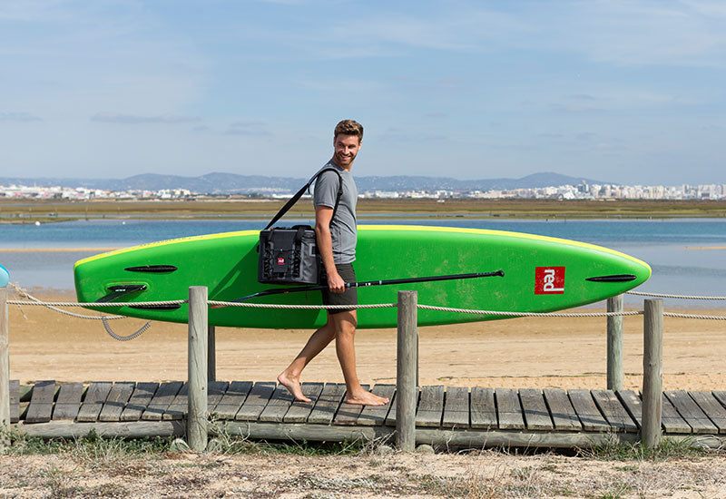 Man carrying a sup whilst wearing the Red Original Mens Performance T Shirt