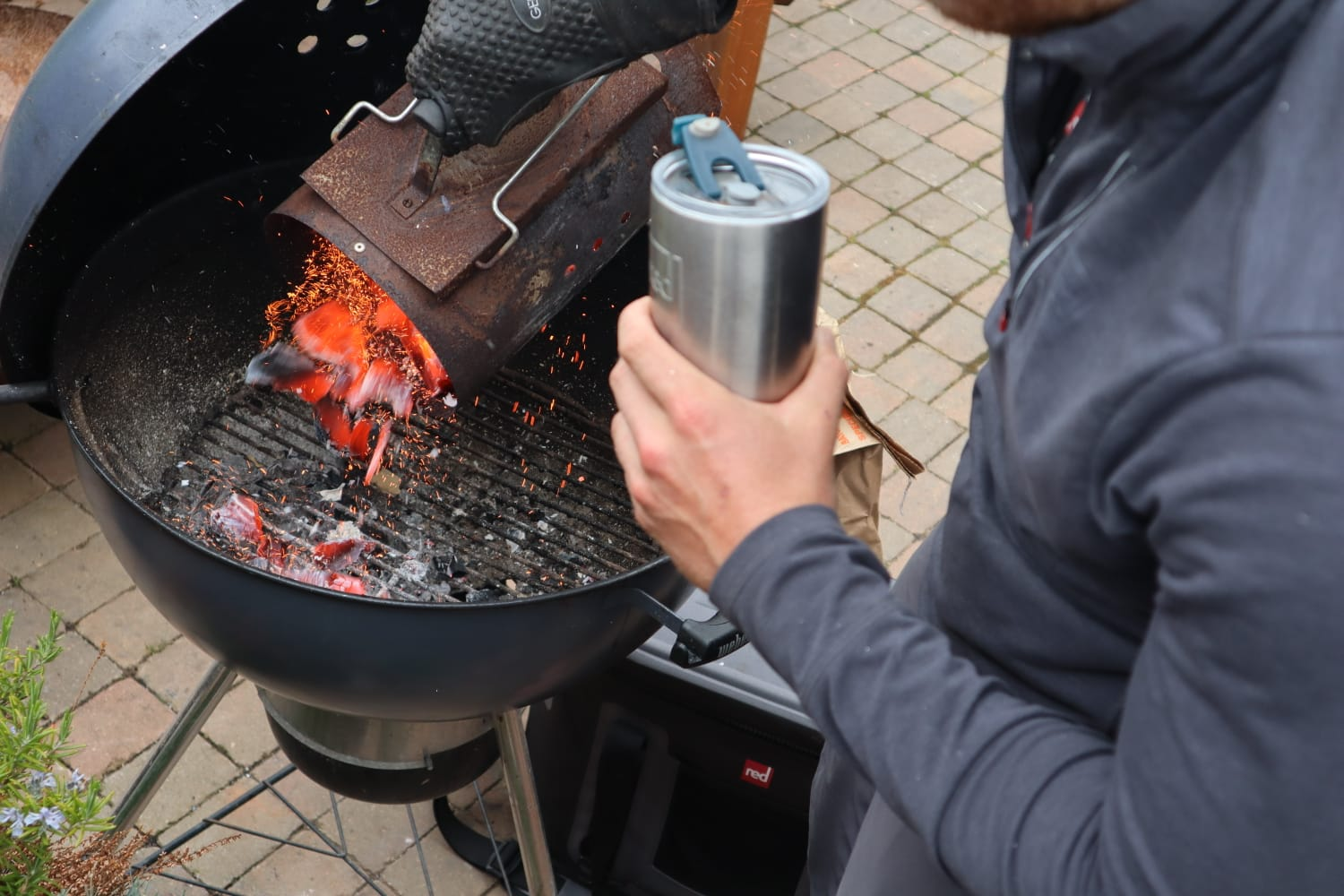 Ross holding travel cup while BBQing