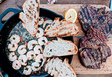 Selection of prawns and steak cooked on a BBQ