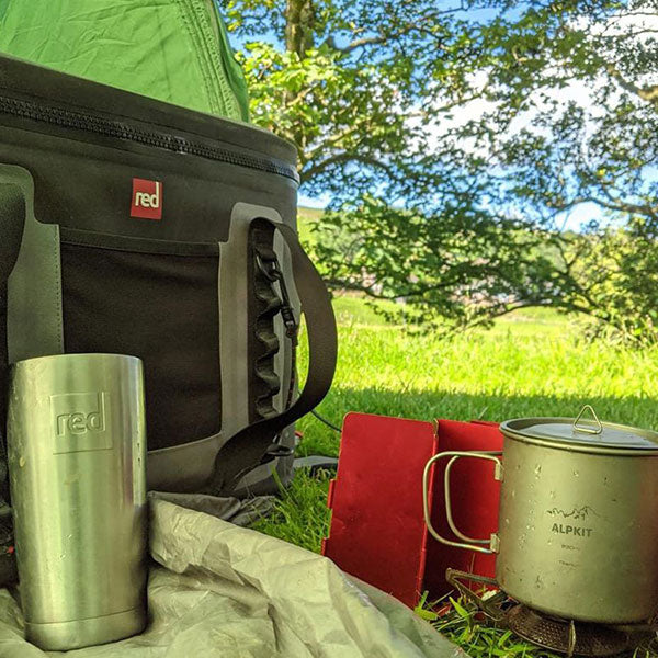 A Red Original Water Bottle and Waterproof cooler bag outside a tent