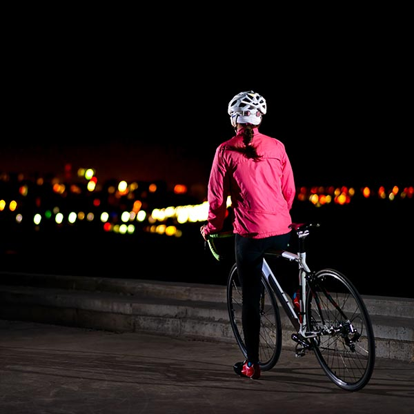 Woman looking out over the city at night while on her bike