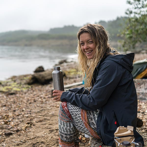 woman sitting at her campsite drinking from an insulated water bottle