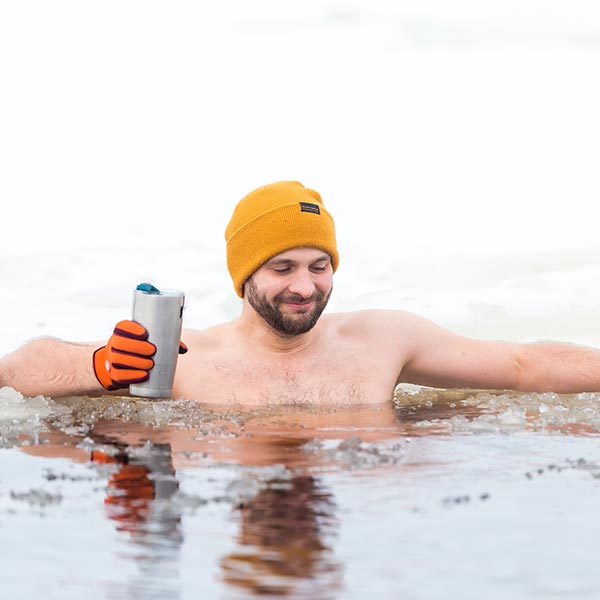 Man sat in cold water wearing an orange beanie hat and holding an insulated travel cup