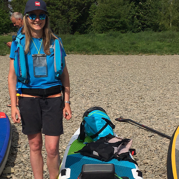 Lucy standing by her loaded paddle board.