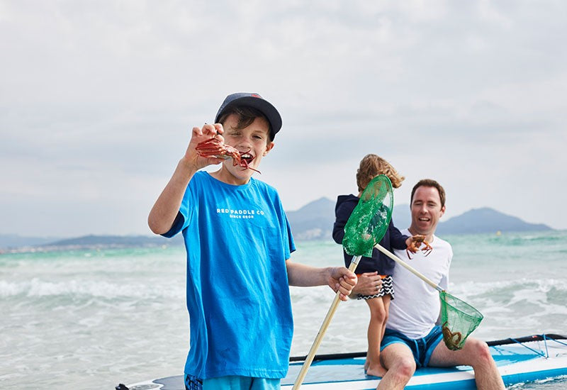 family with fishing nets at beach and child holding crab