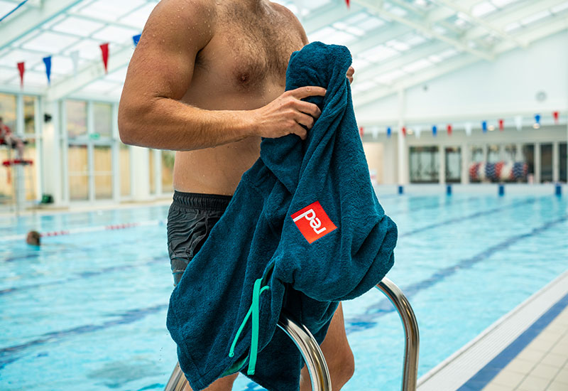 Man getting out of the pool to get changed into Red Original Men's Luxury Towelling Robe - Navy on the railing