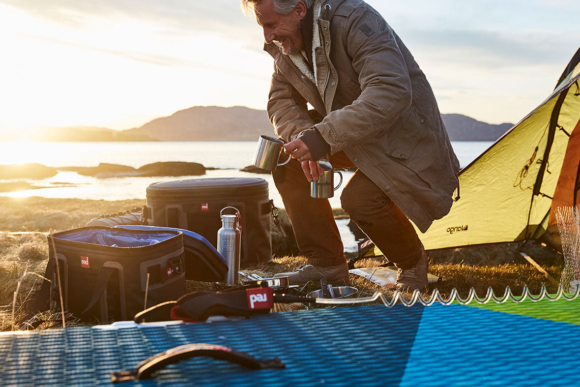 Man Camping On A Beach With 2 Red Original Cool Bags, A Drink Bottle & A Red Paddle Board