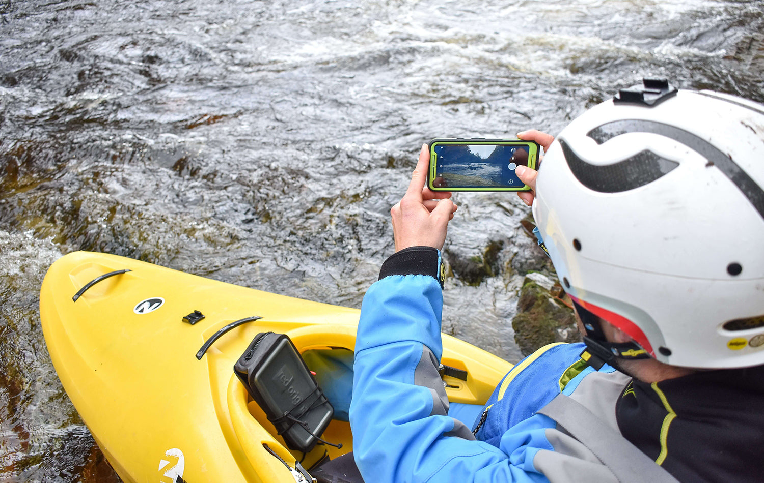 A Man Sat In His Kayak Taking A Photo With His Phone