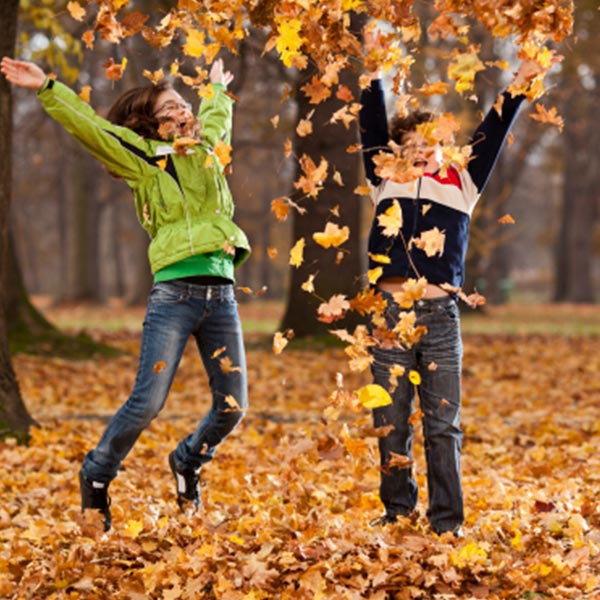 2 women playing and jumping with the leaves