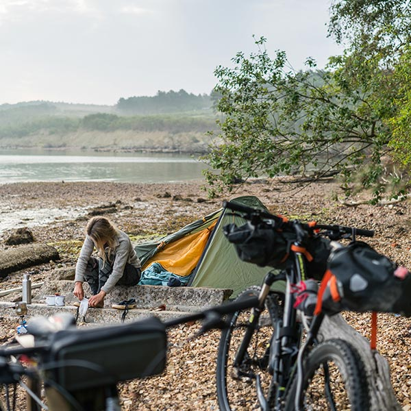Woman camping by a lake with 2 bicycles in the foreground