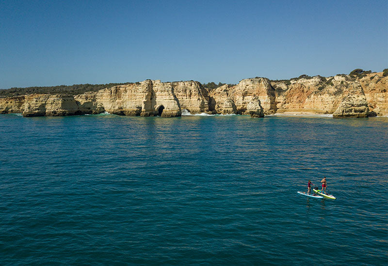 Coupe paddle boarding on the Portugal coastline