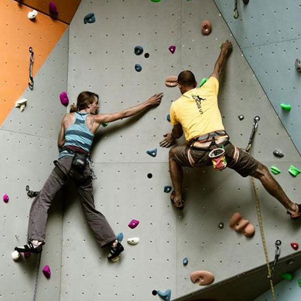 A Couple Climbing Enjoying Indoor Climbing