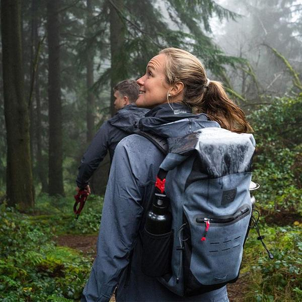man and woman walking through a forest with waterproof backpacks