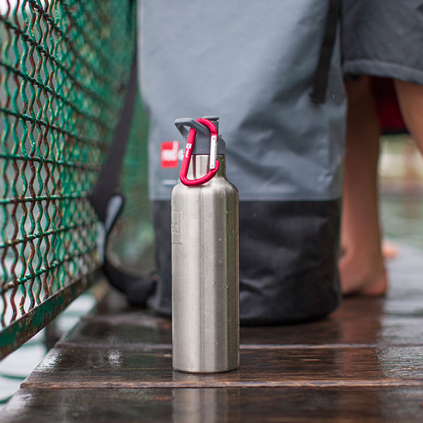 Red Original Marine Grade Stainless Steel Drinks Bottle next to an outdoor swimming pool
