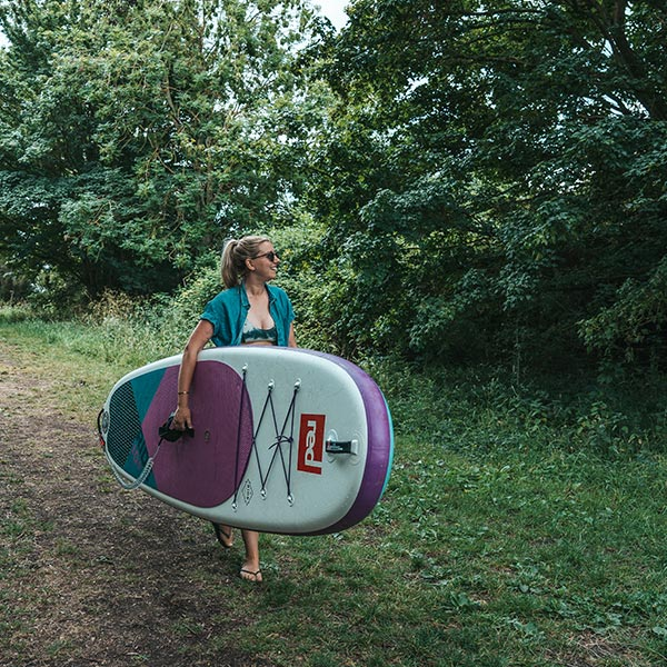 Woman carrying an inflatable paddle board